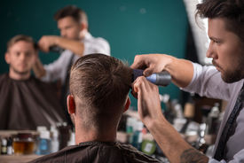 stock photo of shaved head  - hairdresser  cuts    hair  with hair clipper on back of the head of handsome satisfied  client in  professional  hairdressing salon - JPG