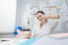 picture of stiff  - Tired female white collar with stiff neck working at desk - JPG