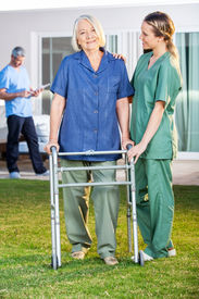 picture of zimmer frame  - Female nurse assisting senior woman to walk with Zimmer frame in lawn at nursing home - JPG