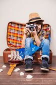 stock photo of little boys only  - Little boy in headwear holding camera and smiling while sitting in suitcase against brown background - JPG