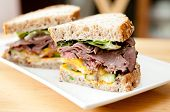 stock photo of deli  - roast beef deli style sandwich on cracked whole wheat bread - JPG