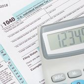 image of cpa  - Calculator over US 1040 Tax Form  - JPG