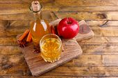 stock photo of cider apples  - Apple cider in glass bottle with cinnamon sticks and fresh apples on cutting board - JPG