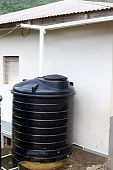 stock photo of downspouts  - Old water cistern collects rain water runoff through the roof downspout - JPG