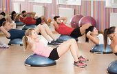 picture of crunch  - Group of fit people doing crunches on bosu - JPG