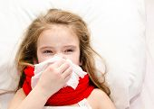 stock photo of sick  - Sick little girl lying in the bed and blowing her nose - JPG