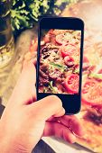stock photo of take out pizza  - Using smartphones to take photos of pizza with instagram style filter - JPG
