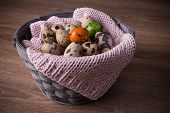pic of quail egg  - Quail eggs in a basket and one orange green egg with pink knit on wooden background - JPG