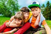 image of three life  - Three joyful children sitting on the grass in the park - JPG