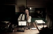 picture of 1950s  - 1950s journalist working late at night in his office typing on a typewriter.