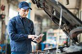 stock photo of overhauling  - Portrait of a mechanic using a tablet in his garage - JPG