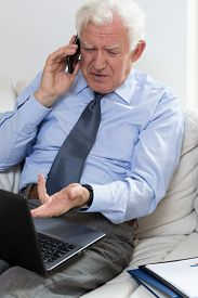 picture of annoying  - Annoyed senior businessman using laptop and talking on the phone - JPG