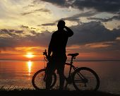 image of dirt-bike  - silhouette of a man with a mountain bike on the river bank at sunset - JPG