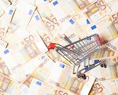 image of fifties  - Tiny shopping cart over the surface covered with the multiple fifty euro bank notes - JPG