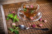 stock photo of rose bud  - Cup of green tea with mint and dried rose buds on old wooden tray - JPG