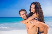 stock photo of piggy  - Man giving piggy back to his girlfriend at the beach on a sunny day - JPG