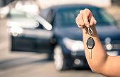 Mans Hand Holding Modern Car Keys Ready For Rental - Concept Of Transportation With Automobile poster