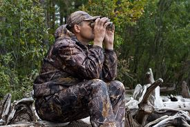 picture of hunter  - hunter looking through binoculars on the river - JPG