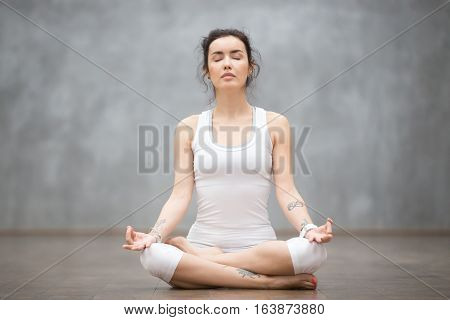 poster of Front view portrait of beautiful young woman with floral tattoos working out against grey wall, resting after doing yoga exercises, sitting in ardha Padmasana, Lotus pose, relaxing. Full length