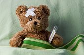 stock photo of pediatrics  - bear in bed with thermometer and plaster - JPG