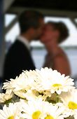 Wedding Couple Kissing Behind Bridal Bouquet, Soft Focus Background poster