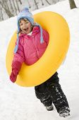 Little girl playing with tube on snow