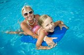 Happy summer vacation - little girl with mother boarding in blue water
