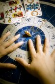 hands of an astrologer over an astrological wheel with tarots and pendulum