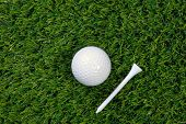A photo of a golf ball and wooden tee on grass