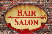 A rusty old retro arrow sign with the text Hair salon