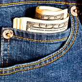 Jeans pocket with many one hundred dollar banknotes in roll