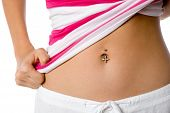 stock photo of pierced belly button  - A woman shows off her belly button piercing - JPG