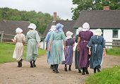 Re-enactment of a pioneer village with a group in period costume.