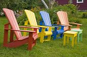 Multi-colored Adirondack chairs in the summer garden.