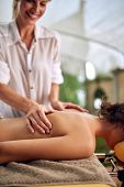 Close up of smiling massage therapist doing a back massage on outdoor poster