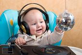 baby with headphones playing with turntable and disco ball