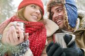 Head And Shoulders Portrait Of Loving Young Couple Enjoying Hot Cocoa During Date In Beautiful Winte poster