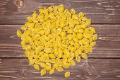Lot Of Whole Raw Yellow Pasta Conchiglie Variety Heap Flatlay On Brown Wood poster