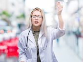 Young blonde doctor woman over isolated background angry and mad raising fist frustrated and furious poster