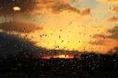 Rain Outside Window On Background Of Sunset. Rain Drops On Glass During Rain. Sunset Outside Window  poster
