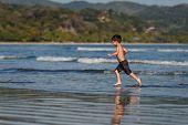 Happy Boy Is Running On Coastline. Ocean poster