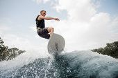 Active Man Jumping Up On The White Wakeboard On The Wave Having Healthy Summertime On The River On T poster