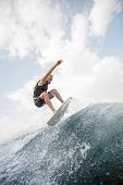 Young Active Man Jumping Up On The White Wakeboard On The Wave Having Healthy Summertime On The Rive poster