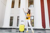 Puzzled Traveler Tourist Woman In Yellow Summer Casual Clothes And Hat With Suitcase Looking On City poster