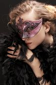 mysterious blond  woman wearing purple  stylish carnival mask and black feathers, role play