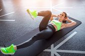 From Above Shot Of Attractive Adult Lady In Sportswear Lying On Floor And Doing Exercise During Work poster
