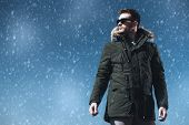A handsome brutal man wearing a parka and sunglasses. Fashion for men. Autumn, winter. poster
