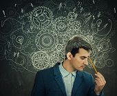 Hard Thinking Serious Man Over Blackboard Background Gear Brain Arrows And Mess As Thoughts. Concept poster