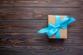 Paper Gift Box With Blue Ribbon On Dark Wooden Background Christmas Present Concept, Top View With C poster