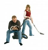 The man is sitting on the vacuum-cleaner and reading a magazine, while the woman is hovering. She ma